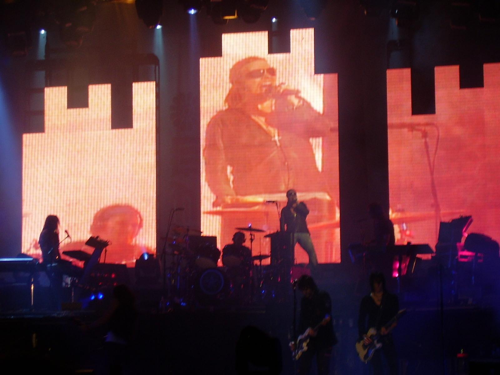 """3f4a4429107 Axl presenta a Dizzy Reed que baja a un piano que acaban de colocar en el  centro del escenario y hace un solo mientras Axl baila detrás de él y  repite """" ..."""